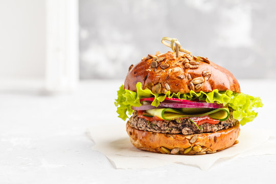 Vegan bean burger with vegetables and tomato sauce, copy space, white background. Healthy vegan food concept.