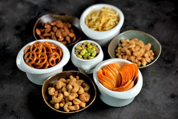 Different kinds of snacks - chips, salted peanuts, cashews, almonds and pistachios, pretzels with salt, potatoes, salted straw.