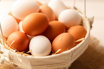 Fresh brown and white chicken eggs in a basket on light wooden table