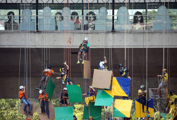 Brazilian climbers prepare to attempt the world record of largest rappel mosaic as they form the Brazilian flag with an image of the World Cup trophy at Sumare bridge in Sao Paulo
