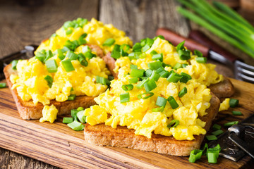 Scrambled eggs with green onion on toasts