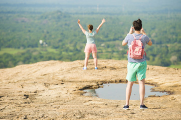 A boy is taking a photo of his girlfriend on top of a mountain near Sigiriya, Sri Lanka. Blurred green vegetation in the background.