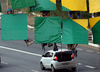 Brazilian climbers prepare to go for the world record of largest rappel mosaic as they form the Brazilian flag with an image of the World Cup trophy at Sumare bridge in Sao Paulo