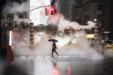 A woman with an umbrella and red high heels shoes is crossing the 42nd street in Manhattan. Taxi...
