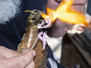 Lampwork - Craftsmans hands forming glass fairy by melting glass with a torch in the form of a dragon