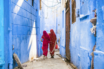 Two women dressed in the traditional Indian Saree are walking through the narrow streets of the blue city of Jodhpur, Rajasthan, India. Fotomurales