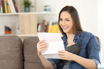 Happy woman holding a letter at home