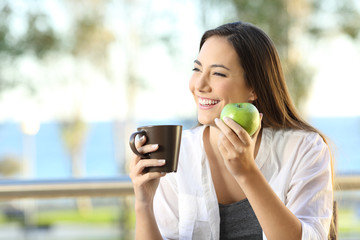 Happy woman holding an apple and a coffee mug