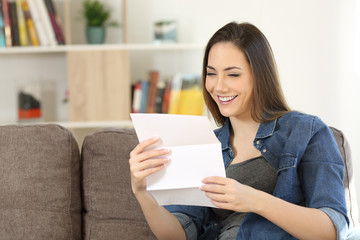 Happy woman reading a letter on a couch at home