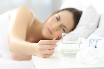 Ill woman holding a painkiller pill on a bed