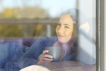 Relaxed woman looking outdoors through a window