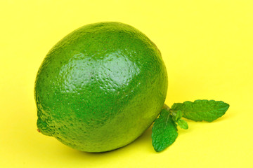 Fresh lime with mint on yellow background
