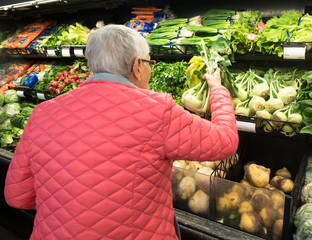 An Elderly Woman Shopping for Kohlrabi in the produce section of the supermarket.  She is wearing a bright pink jacket.