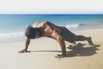 Workout exercise concept.Healthy Handsome Active Man With Fit Muscular Body Doing Push Ups Exercises. Sporty Athletic Male Exercising At Beach. Training Outdoor. Sports And Fitness Concept.