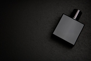 Mockup of black fragrance perfume bottle mockup on dark empty background. Top view. Horizontal Wall mural
