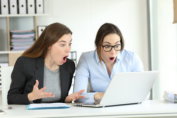 Surprised office workers reading online news