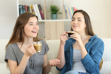 Two friends talking and enjoying a coffee cup