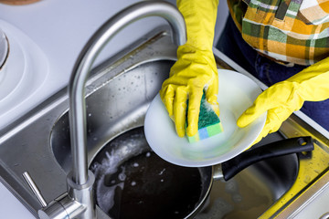 cropped image of woman washing plate with washing sponge in kitchen