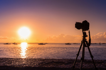 silhouette of camera on tripod shooting sea with sunset.
