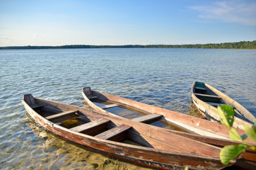 Old wooden fishing boats on the lake beach with blue sky.