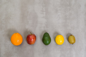 Great concept of healthy eating, various fruits on gray background, polished concrete. Orange, apple, kiwi, lemon.