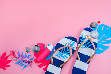 Beach accessories, flip flops, tropical leaves, seashells flat lay. Colorful travel and vacation concept on a bright pink background with copy space.