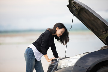 Stressed women  after a car breakdown with Red triangle of a car on the road