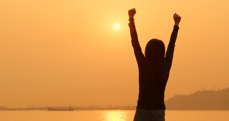 Woman raising hand up under sunset