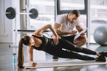 Male personal trainer looking at timer and young athletic woman doing side plank on fitness mat Wall mural