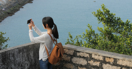 Woman taking photo with the sea