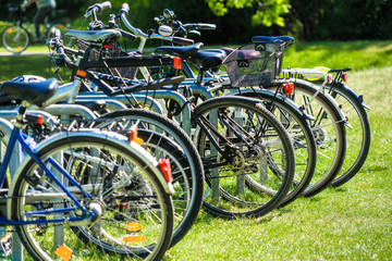 Abstracted image with intentionally low depth of field from a group of bicycles parked on the lawn of a public park