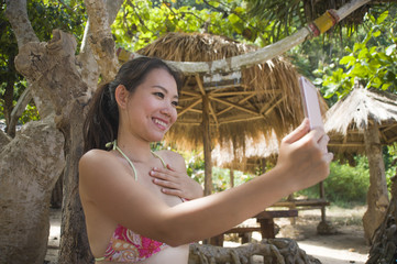 young beautiful and happy Asian Korean woman taking self portrait selfie with mobile phone at tropical paradise beach resort under palm trees shade