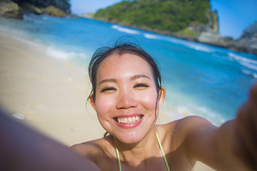 young happy and beautiful Asian Korean or Chinese tourist woman in bikini taking self portrait selfie photo with mobile phone at tropical paradise beach