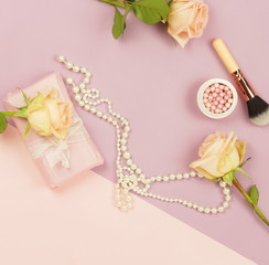 Pink ranunculus flowers, gift box and pearl necklace on blue pale pink background. Top view. Copy space