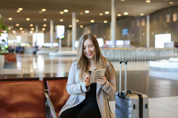 European woman using internet by modern tablet in airport waiting room near grey valise. Concept of social networks, free hotspot and gladden passenger.