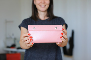 Female person standing with pink leather handmade wallet at home atelier. Concept of handicraft goods.