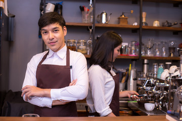 Asian male barista loking to camera with attractive smile in coffee shop counter.  Barista male working at cafe. Man working with small business owner or sme concept.