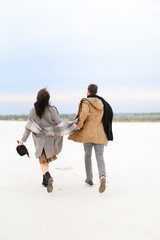 Happy american couple walking in winter white background, holding hands and wearing coats. Concept of seasonal inspiration and couple photo session.