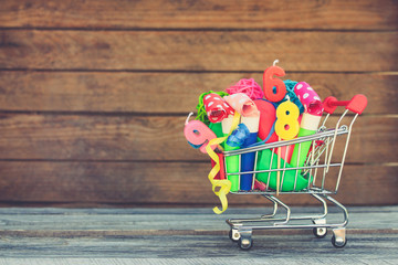 Shopping cart with items for birthday celebration on wooden background. Toned image.