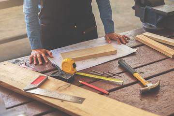 Carpenter working on woodworking machines in carpentry shop. woman works in a carpentry shop.