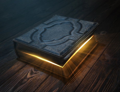 Old magic book on wooden table with light rays coming out form inside