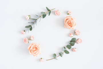 Flowers composition. Wreath made of rose flowers, eucalyptus branches on pastel gray background....