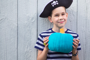 happy boy in a pirate costume with a teal pumpkin in his hands. Teal Pumpkin Project. Alternative non-food treats for kids with food allergies. the concept of health for children in the Halloween