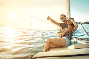 Romantic couple in love on sail boat at sunset under sunlight