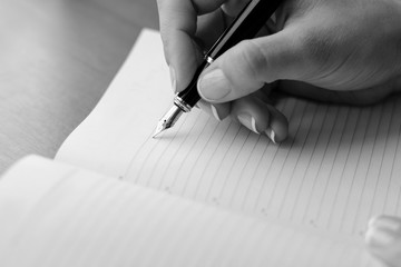 Woman (girl, bussineswoman) hand with pen writing on notebook.