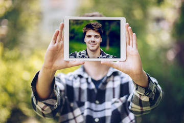 detail shot of a handsome young man taking a selfie with a tablet, smiling and waving at the camera.