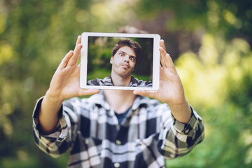 detail shot of an attractive and handsome young man taking a selfie with a tablet, making a silly spontaneous face.