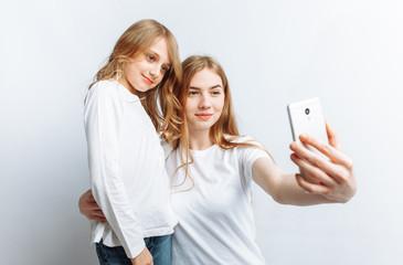 Mom or older sister makes selfie little girl, happy family, photo Studio, isolated