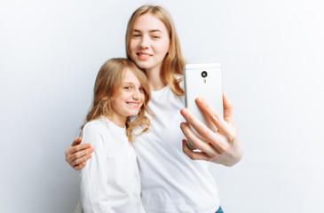 Mom or older sister makes selfie little girl, happy family, photo Studio, isolated