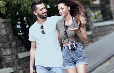 Cheerful young couple walking on urban street